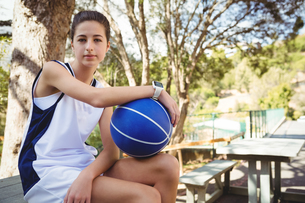 Portrait of female basketball player sitting on picnic tableの写真素材 [FYI02237274]