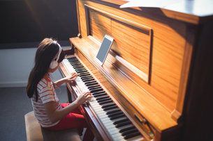 High angle view of concentrated girl practicing pianoの写真素材 [FYI02237283]