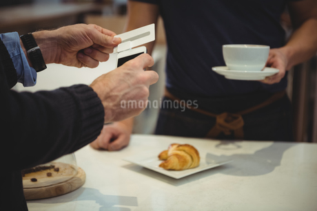 Customer making payment with smartphone in coffee shopの写真素材 [FYI02237284]