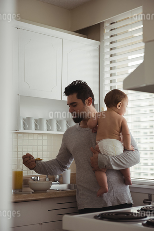 Father having breakfast while holding his babyの写真素材 [FYI02237329]