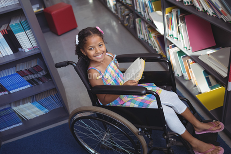 Portrait of smiling girl with book on wheelchairの写真素材 [FYI02237331]