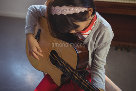 High angle view of girl practicing guitarの写真素材 [FYI02237345]