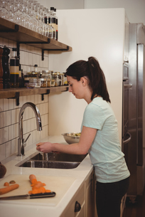 Female chef washing carrot under the tap in professional kitcheの写真素材 [FYI02237361]