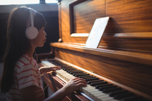 Girl looking at digital tablet while practicing piano in classroomの写真素材 [FYI02237372]