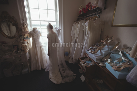 Young bride in a white dress looking through the windowの写真素材 [FYI02237383]