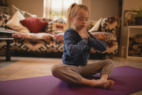 Girl performing yoga in living roomの写真素材 [FYI02237389]