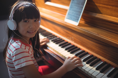 High angle portrait of girl wearing headphones while practicing pianoの写真素材 [FYI02237416]