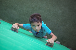 Portrait of boy climbing green wallの写真素材 [FYI02237447]