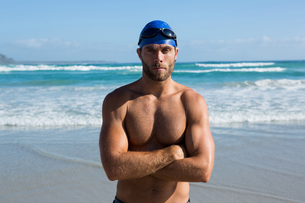 Portrait of shirtless athlete standing at beachの写真素材 [FYI02237467]