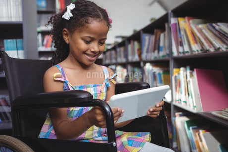 Girl on wheelchair using digital tablet in libraryの写真素材 [FYI02237505]