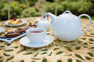 Cup of tea with dessert and teapot on tableの写真素材 [FYI02237515]