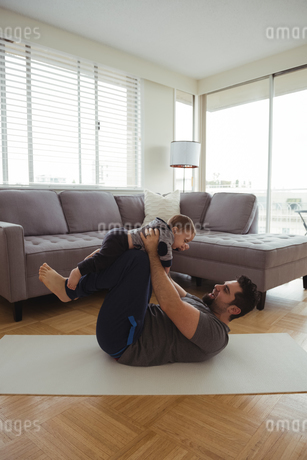 Father playing with his baby in living roomの写真素材 [FYI02237557]
