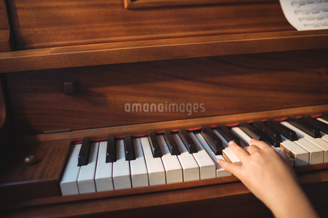 Cropped hand of girl practicing pianoの写真素材 [FYI02237566]