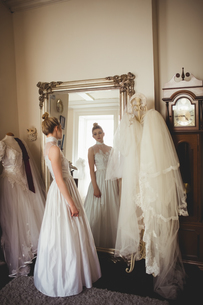 Young bride in a white dress looking into mirrorの写真素材 [FYI02237567]