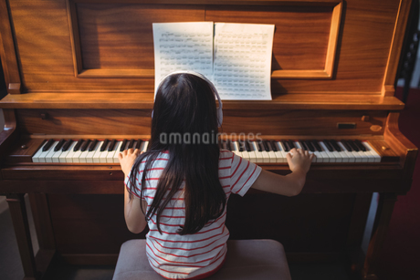 Rear view of girl practicing piano in classroomの写真素材 [FYI02237575]