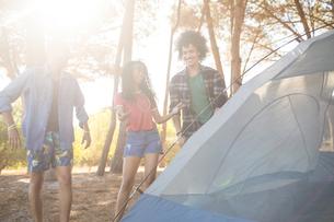 Happy friends standing by tentの写真素材 [FYI02237583]