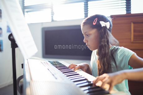 Concentrated elementary girl practicing pianoの写真素材 [FYI02237591]