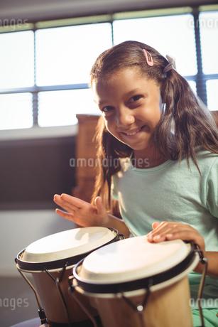 Portrait of smiling girl playing bongo drumsの写真素材 [FYI02237615]