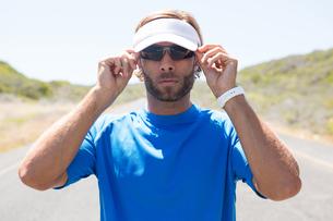 Male athlete wearing sunglasses on roadの写真素材 [FYI02237620]