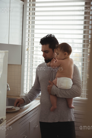 Father preparing breakfast while holding his babyの写真素材 [FYI02237627]