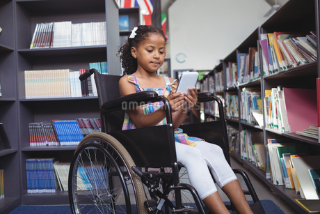 Girl using digital tablet on wheelchair in libraryの写真素材 [FYI02237656]