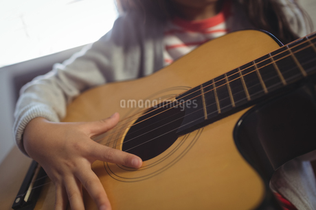 Mid section of girl practicing guitarの写真素材 [FYI02237680]
