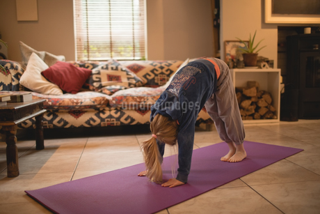 Girl performing yoga in living roomの写真素材 [FYI02237691]