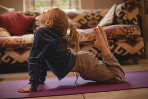 Girl performing yoga in living roomの写真素材 [FYI02237699]