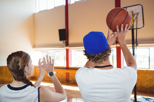 Rear view of coach training basketball player in courtの写真素材 [FYI02237730]