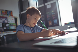 Boy writing in book on deskの写真素材 [FYI02237743]