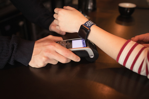 Woman paying through smartwatch using NFC technologyの写真素材 [FYI02237744]