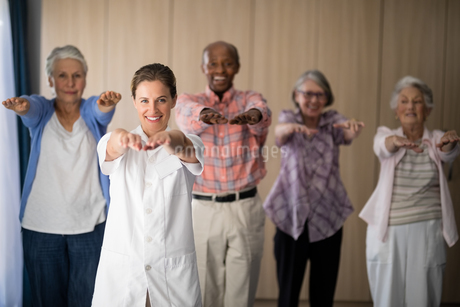 Portrait of smiling female doctor and seniors exercisingの写真素材 [FYI02237770]