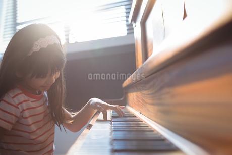 Elementary girl practicing piano in classの写真素材 [FYI02237777]