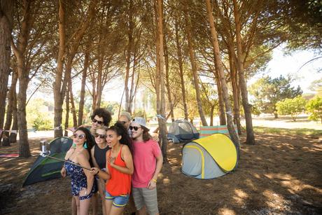 Friends taking selfie with selfie stick at campsiteの写真素材 [FYI02237779]