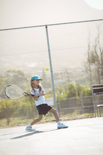 Girl playing tennis against fenceの写真素材 [FYI02237789]