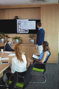 Business people looking at device screen during meetingの写真素材 [FYI02237804]