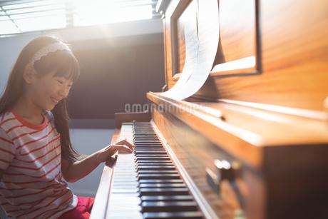 Smiling girl practicing piano in classの写真素材 [FYI02237812]