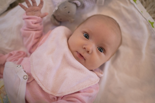 Close-up of cute baby lying on bed sheetの写真素材 [FYI02237816]