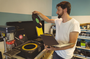 Worker holding record by turntable at workshopの写真素材 [FYI02237825]