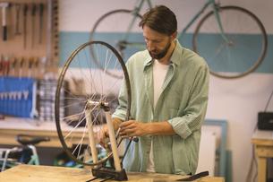 Worker repairing wheel on table at workshopの写真素材 [FYI02237826]
