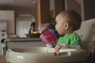 Baby girl drinking water from a baby bottle in kitchenの写真素材 [FYI02237838]