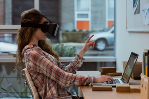 Female executive using virtual reality headset while working on laptop at deskの写真素材 [FYI02237892]