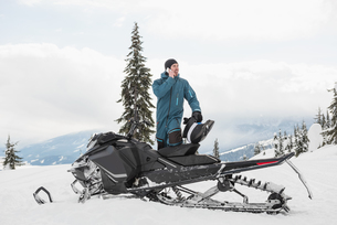 Man talking on mobile phone while standing near snowmobile in snowy alpsの写真素材 [FYI02237935]