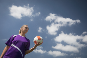 Woman holding soccer ball against skyの写真素材 [FYI02238001]