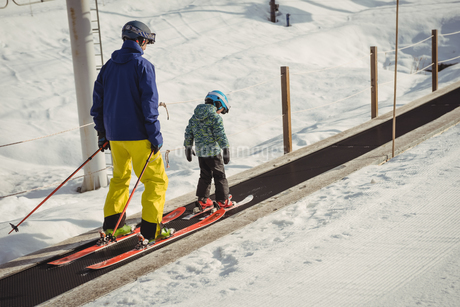 Father and daughter skiing on conveyor beltの写真素材 [FYI02238077]