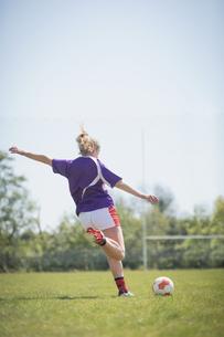Rear view of woman kicking soccer ballの写真素材 [FYI02238096]