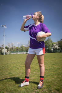 Thirsty soccer player drinking water on fieldの写真素材 [FYI02238152]
