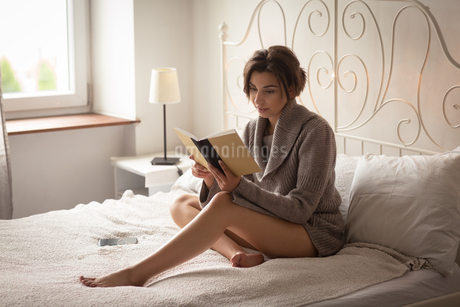 Woman reading book while sitting on bedの写真素材 [FYI02238154]