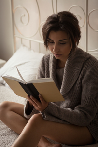 Close up of woman reading book at homeの写真素材 [FYI02238156]