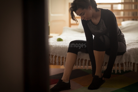 Woman wearing shoes while sitting on bedの写真素材 [FYI02238177]